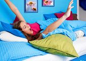 young girl yawing in bed before standing up