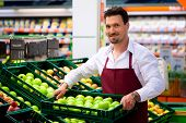 Man in supermarket as shop assistant; he brings some boxes with apples