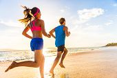 Runners fitness couple running training on beach. Morning cardio workout people doing exercise.Activ poster