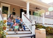 Family Sitting On Steps Of New Home On Moving In Day poster