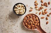 Peeled (blanched) and unblanched whole almonds. Shelled almonds on a spoon with a small black bowl o poster