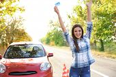 Young happy woman holding driving license near car poster