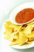 picture of doritos  - Plate of nachos and hot salsa dip sauce