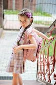 stock photo of bagpack  - Young school girl with pink bagpack waits standing on stairs - JPG