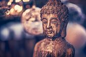 Vintage style photo of the wooden statue of Buddha, God of oriental religion, conceptual picture of  poster