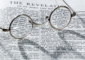 image of revelation  - Old fashioned round reading glasses laying on a page from the bible on the revelation with strong shadow - JPG