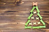 Christmas Tree Maden From Canine Chewing Bones And Cookies On Wooden Background poster