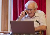 Old Elderly Senior Man On Phone At Laptop Computer At Risk To Cyber Attack And Online Bank Fraud poster