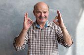 Senior Bald Hispanic Man Showing Ok Sign poster