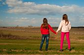 Two teenage girls standing and holding hands while watching the nature on beautiful sunny spring day