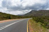 Empty Countryside Road With Warning Road Sign Of Sharp Road Bend Ahead With Picturesque Mountains On poster