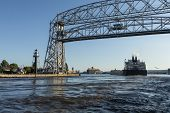 A Ship Entering Harbor Under A Lift Bridge On Lake Superior. poster