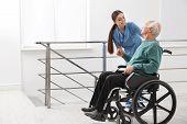 Nurse Assisting Senior Man In Wheelchair At Hospital poster