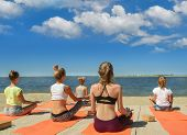 Group Young Womans Yoga Practice Relaxation In-class Exercise On The Beach And Seaside. poster