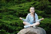 Child Girl Meditating In The Park. Healthy Lifestyle. Meditation And Yoga Concept. Selective Focus. poster