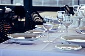 Table Setting In Restaurant. Empty Wine Glasses, Plates, Forks, Knifes On The Tablecloth. Elegant Re poster