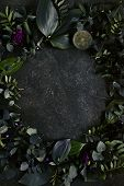 Dark green tropical leaves on natural black stone background with copyspace top view. Round frame ma poster