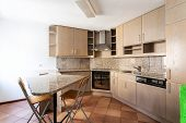 Modern light kitchen with island and stools. Nobody inside poster