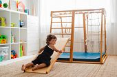 Child At An Early Age Of 1.5 Years Is Engaged In The Home Childrens Wooden Sports Complex With A Sli poster