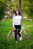 Sports Girl Rides A Bicycle. Emotions And Lifestyle. Young Beautiful Woman Riding A Bike In The Park poster