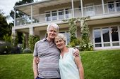 Portrait of senior couple embracing each other in lawn poster