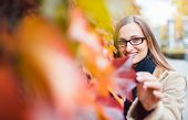 Beautiful woman hiding behind red ivy leaves in fall in a playful manner poster
