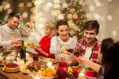 holidays and celebration concept - happy friends having christmas dinner at home, drinking red wine  poster