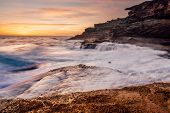 Large Waves Smash Against The Rocky Coastline Of Sydney With A Beautiful Sunrise Colouring Light Clo poster