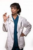 picture of flu shot  - Attractive mixed race young brunette woman nurse or doctor wearing scrubs standing over white holding a syringe - JPG