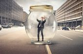 Young businessman trapped in a glass jar in the middle of a city street
