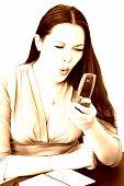 Joven enojada con teléfono celular y agenda