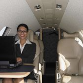 Businesswoman working on laptop inside airplane
