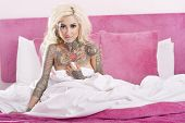 foto of partially nude  - Portrait of a tattooed woman covering herself bed sheet - JPG