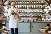 stock photo of apron  - Portrait of a happy senior merchant standing with spice jar in store - JPG