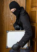 Male Burglar Stealing Case With Money