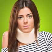 picture of neck brace  - Young woman with neck brace against a green background - JPG