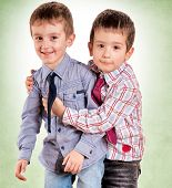 foto of fraternal twins  - Strong brother hug on  the green background - JPG