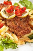 Viener schnitzel, breaded steak with french fries, lettuce and tomato