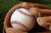 Well worn baseball glove with new ball on grass. Highly detailed closeup image taken in soft side-li