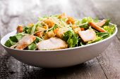 image of caesar salad  - Caesar salad with chicken and greens on wooden table - JPG