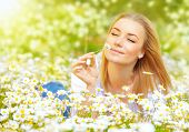 Photo of pretty blonde woman lying down in chamomile field, cute female enjoying smell of daisy, sweet teenager girl with closed eyes relaxed on flowers meadow, spring nature, having fun outdoor