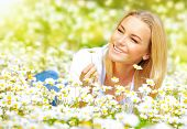 Image of sweet girl lying down on daisy glade and enjoying warm sun light, beautiful woman holding i