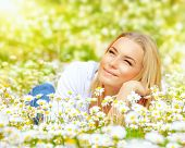 Photo of cute blond female laying down on chamomile field and looking up in sky, sunny day, warm wea