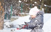 Little girl is throwing snow playing outdoors