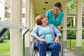 Senior woman in wheelchair talking to a nurse in a hospital garden