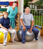 Two senior people sitting on gym ball in physiotherapy