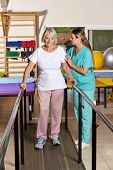 Senior woman holding railing in physiotherapy with a nurse