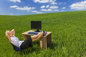 Business concept shot of a beautiful young woman businesswoman relaxing with her feet up at a desk with a computer in a green field with a bright blue sky