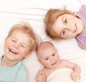 picture of three sisters  - Closeup portrait of three cheerful kids lying down at home - JPG
