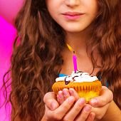 Lovely birthday girl make a wish with sweet festive cupcake in hands, enjoying holiday celebration,